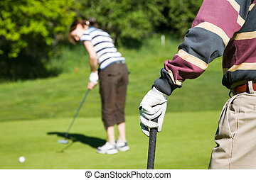 Golfing - Senior man playing golf with his grandaughter
