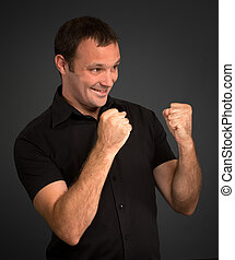 Boxing - Portrait of a man in black in a boxing gesture
