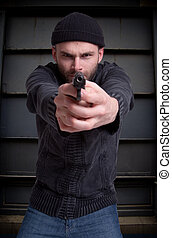 Thug - Dangerous looking man holding a gun aiming at you in...