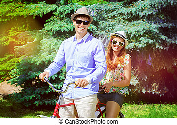resting spring - Happy young couple in summer park rides a...