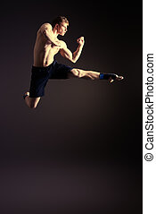 champion jump - Man in sportswear performing a kick Martial...