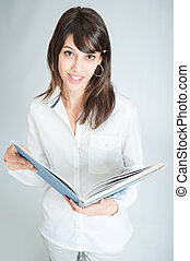 Smiling brunette in white shirt with book - Young brunette...