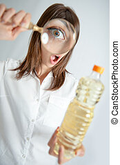 Bottle inspection - Young woman inspecting a bottle of oil...