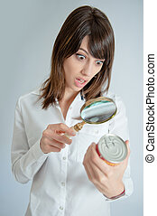 Shocked woman inspecting a nutrition label - Shocked young...