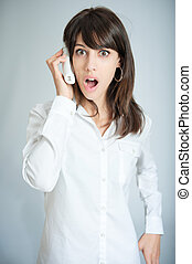 Shocking news - Young brunette talking on the phone with a...