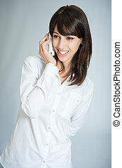 Happy phone call - Young brunette talking on the phone with...