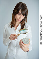 Woman inspecting nutrition label - Young woman inspecting a...