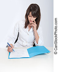 Healthcare paperwork - Serious young woman in a lab coat...