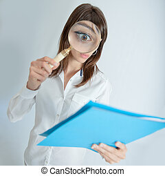 File inspection - Young woman looking to a file through a...