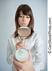 Woman scrutinizing nutrition label - Young woman inspecting...