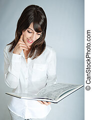 Daydreaming with book - Young brunette reading a book with a...