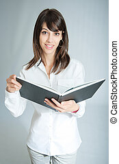 Smiling brunette with an open book - Young brunette wearing...