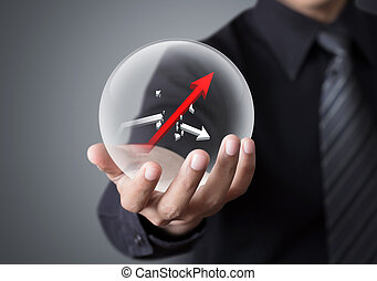 Businessman holds crystal ball with rising red graph and...