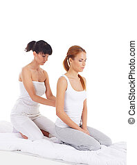 Young woman getting traditional thai stretching massage by...