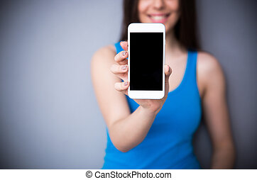 Woman showing blank smartphone screen. Focus on smartphone