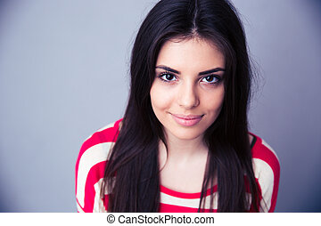 Portrait of a pretty young woman over gray background....