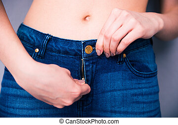 Closeup image of a female hands unzip jeans over gray...