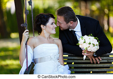 Happy bride and groom - Bride and groom embracing on a swing...