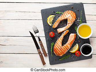 Grilled salmon, salad and condiments on wooden table Top...