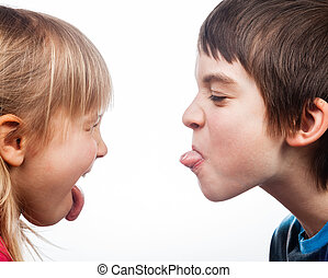 Siblings sticking out tongues - Close-up shot of boy and...