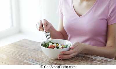 close up of young woman eating salad at home - healthy...