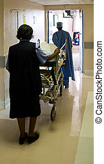 Hospital emergency - Healthcare personnel carry one patient;...