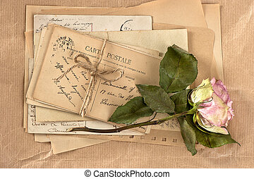 dry rose and old letters vintage postcards and envelopes