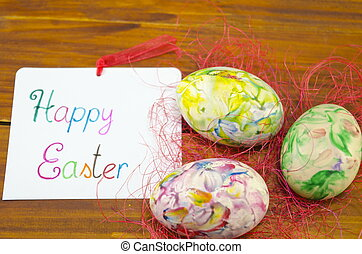 Happy Easter card with hand painted Easter eggs on a wooden...