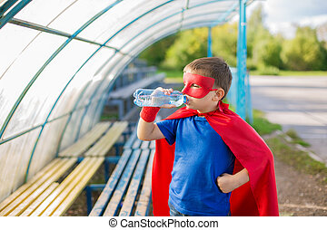 Superhero standing under canopy and drinking water from a...