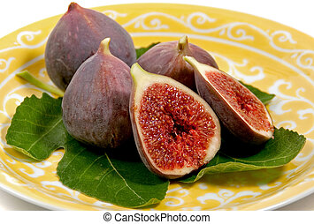 a plate figs on a fig leaf - a plate of fresh figs arranged...