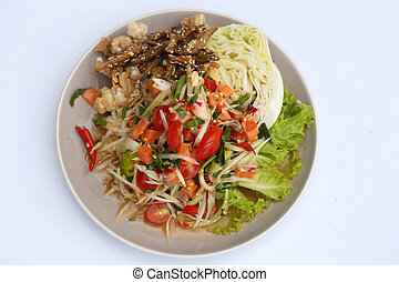 papaya spicy salad with salmon on white table in restaurant