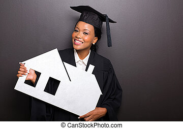african female university graduate holding paper house -...