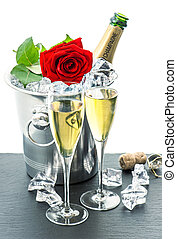 two glasses, bottle of champagne and red rose flower festive...