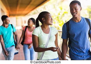 african college students walking in building corridor -...
