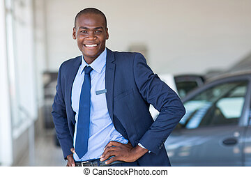 young african american car dealership principal standing in...