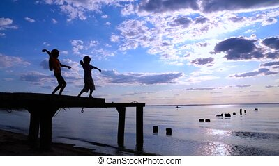 Two kids throwing the stones to sea