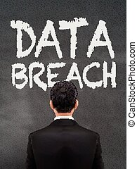 businessman looking at data breach words on wall