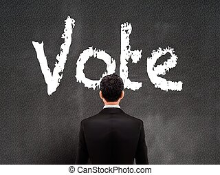 businessman looking at vote word on wall