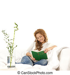 Young beautiful woman reading book on the sofa