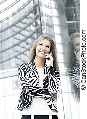 Woman talking on the phone over urban background