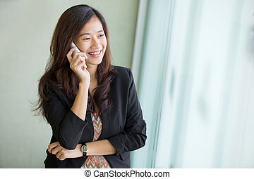 young woman talking on the phone while standing next to a window
