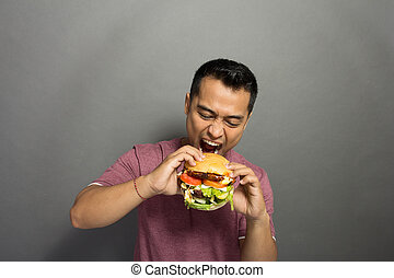 Young Man have a great desire to eat a burger - A portrait...