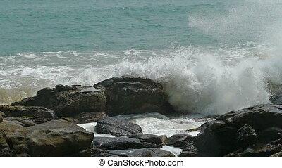 big waves crashing on stone beach - slow motion