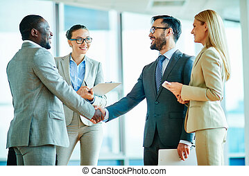 New deal - Two successful businessmen handshaking with...