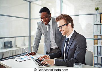 Entering data - Happy young businessman typing on laptop at...