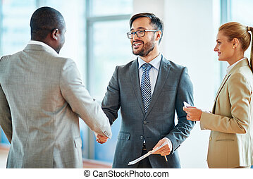 Business agreement - Happy businessmen handshaking after...