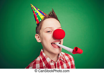 Birthday fun - Funny kid with red nose having fun on...