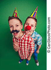Hilarious twins with clown nose and moustache during fool?s...