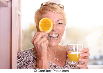 Laughing woman holding an orange to her eye - Laughing...