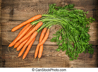 Carrots on rustic wooden background. Country style food...